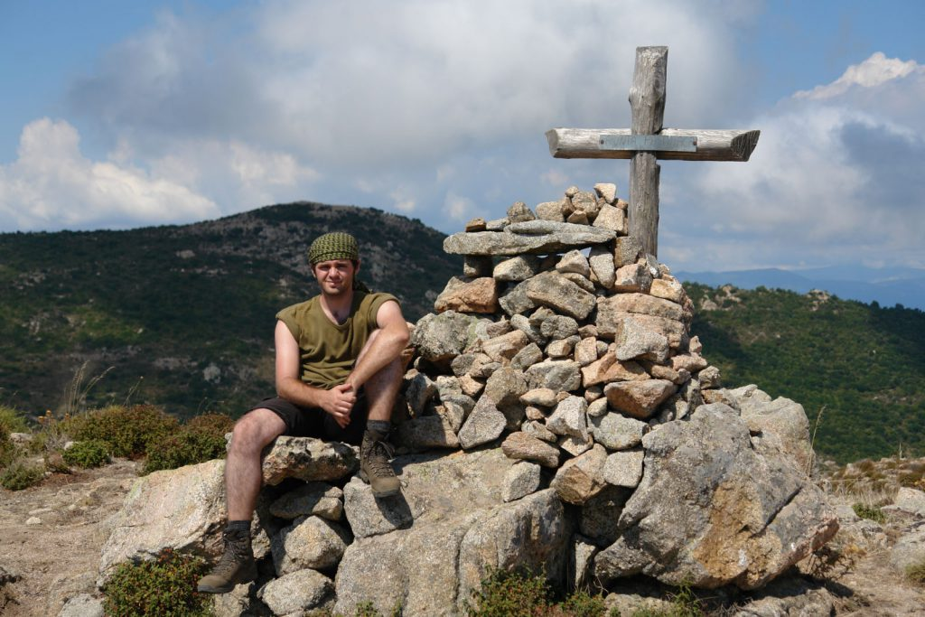 Pierre neben einem Gipfelkreuz mit Shemagh als Sonnenschutz auf dem Kopf